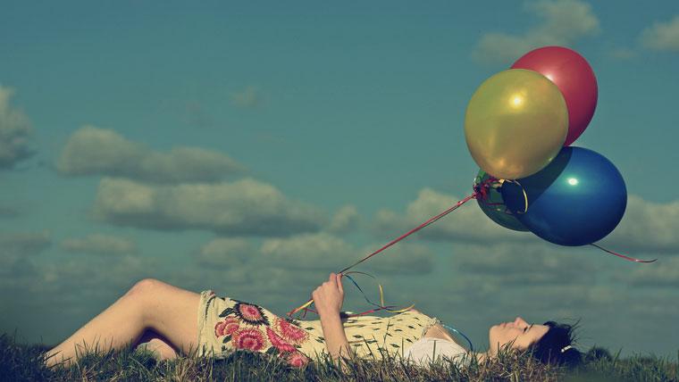 Ragazza rilassata su un prato con dei palloncini colorati