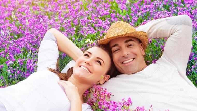 Coppia distesa in un campo di fiori viola, felice per i risultati ottenuti con la Disintossicazione secondo il proprio biotipo