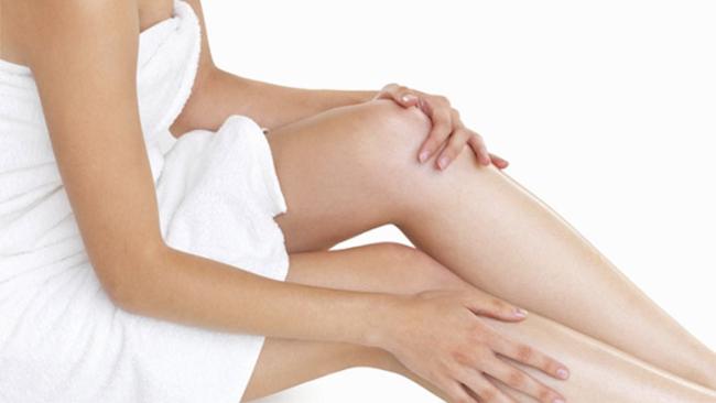 Donna con asciugamano bianco applica un olio corpo