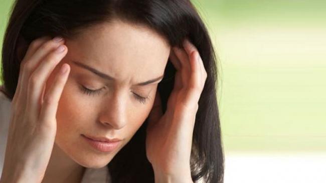 Donna con mail di testa, sintomo della stitichezza