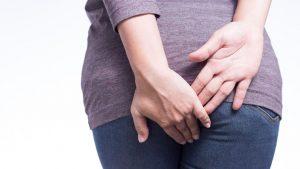 Donna con mani sul sedere prova dolore a causa delle emorroidi
