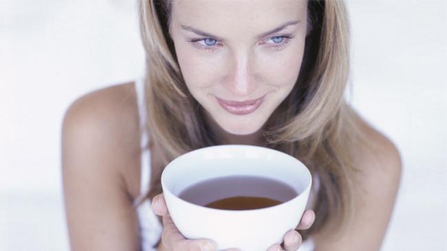 Giovane donna beve una tazza di te terapeutico